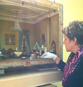 Jolie Gaston making adjustments in the Victorian Parlor, Thorne rooms, Knoxville Museum of Art.