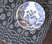 1/12 scale Delftware plate by Henny Staring-Egberts, Fellow member, on a silk woven coverlet by Bonni Backe, Fellow member.