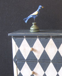 1/12 scale folk art bird by Mary Grady O'Brien, Fellow member, atop a painted chest of drawers by James Hastrich, Fellow member.