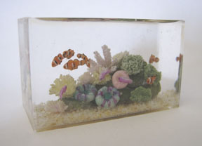 1/12 scale clownfish swim among colorful corals in an aquarium by IGMA Artisan member Miyuki Kobayashi.