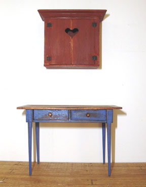 A wall cupboard with a whimsical heart cut-out over a country table with drawers, both in 1/12 scale.