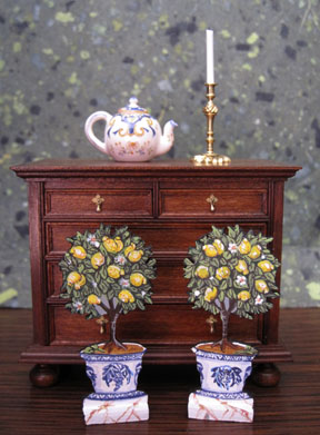 A pair of Terence Stringer dummy boards from Mary Katherine Johnson MIniatures, a French faience teapot from Jack Cashmere of Cashmere's Collectibles and a brass candlestick from Bill Robertson.