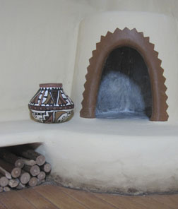 Kiva-style fireplace with banquette and built in woodbox in the corner of the adobe roombox.
