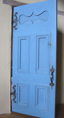 Handmade paneled door on adobe roombox.