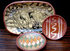 Red ware with a variety of decorative glazes in 1/12 scale by Jane Graber of Graber Gallery.