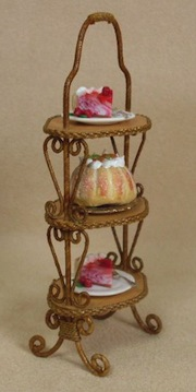 An English wicker cake stand in 1/12 scale by Vickie Sanford of Uncle Ciggie's Miniatures.