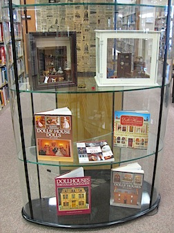 A  display case at the Hartsville Public Library with miniatures and related reading material.