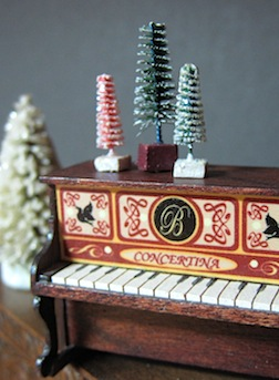 Brush trees atop a 1/12 scale toy piano made by Tracey Meeker.