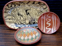 Three pieces of redware decorated in different ways, graffito, slipware and the platter in the back is done with a marble effect glaze.