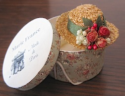A straw hat and box by international doll artist Marie France Beglan, another of the 35 Give-Aways.