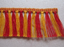 Two color tape with woven in fringe trim in 1/12 scale.