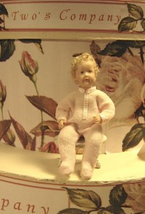 A toddler in a pink one-piece by Two's Company Miniatures. Find Jennifer and Elizabeth Ellis at table 38.